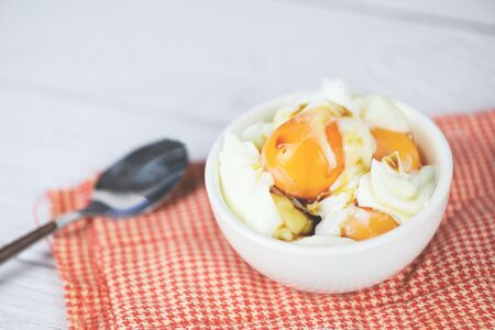 boiled egg on bowl with sauce for breakfast on the table background / Soft boiled eggs