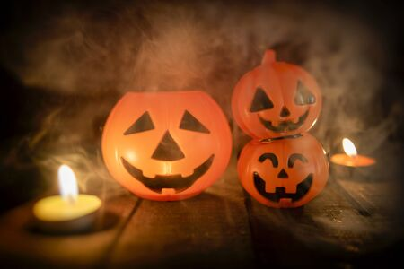 Halloween pumpkin lantern candle light on wooden with smoke  head jack o lantern funny faces spooky holiday decorate on halloween background Zdjęcie Seryjne