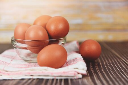 Fresh egg bowl on tablecloth on the wooden table background / Raw chicken eggs collect from the farm products natural eggs for food