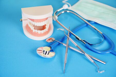 dentist tools with dentures dentistry instruments and dental hygienist checkup concept with teeth model and mouth mirror oral health and stethoscope doctor