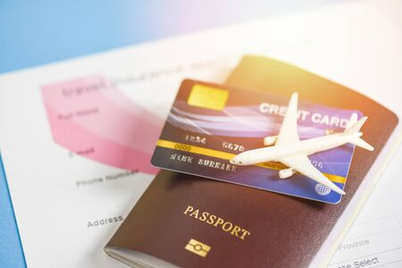 Travel insurance application form with  passport credit cards airplane flight travel traveller fly travelling citizenship air boarding pass travel business trip