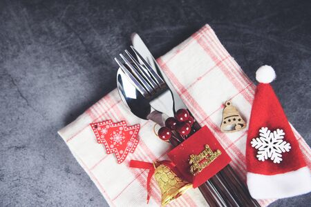 Christmas table place setting decoration with santa claus hat fork spoon and knife on tablecloth napkin Xmas New Year food lunch festive Christmas dinner holidays background themed party