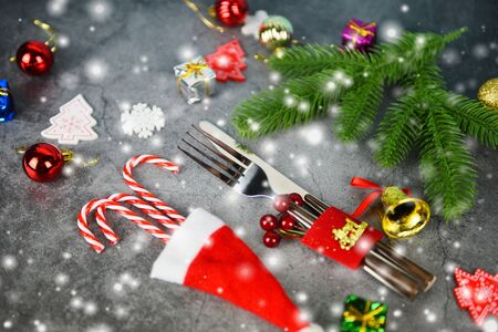 Christmas table place setting decoration with gift box ball candy cane in santa claus hat fork and knife Xmas New Year food lunch festive Christmas dinner holidays background themed party with snow