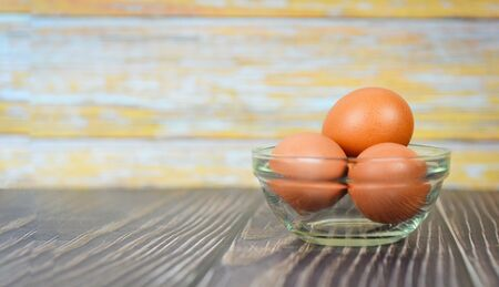 Fresh egg glass bowl on the wooden table background / Raw chicken eggs collect from the farm products natural eggs for food Standard-Bild
