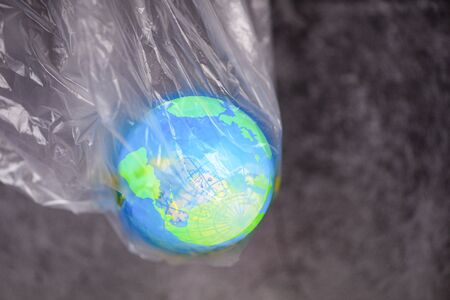 Plastic world or World Environment Day Concept  The planet earth in a plastic bag ban say no plastic pollution zero waste recycle Banco de Imagens