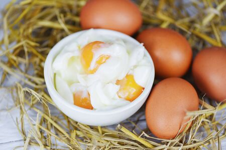 boiled egg on bowl and fresh eggs on straw background / Soft boiled eggs