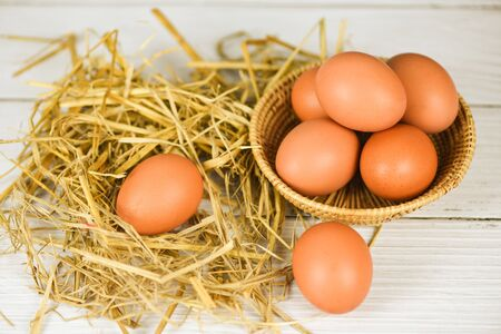 Fresh egg on basket and straw with wooden table background top view  Raw chicken eggs collect from the farm products natural eggs Stok Fotoğraf