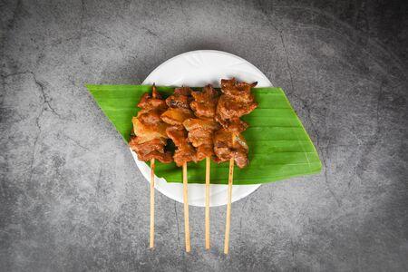 Grilled pork thai asian street food style  Slice pork skewer sticks grilled on banana leaf on white plate