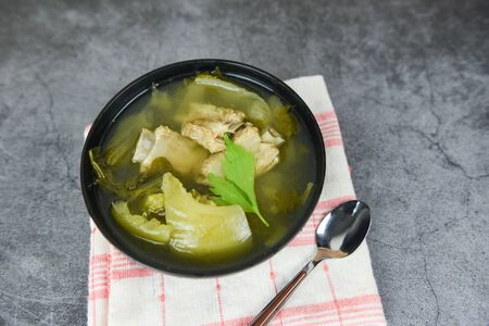 Pickled lettuce soup with spare ribs pork bone soup bowl with vegetable on dining table Imagens
