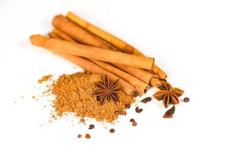 Cinnamon sticks and Star Anise on cinnamon powder herbs and spices on white background