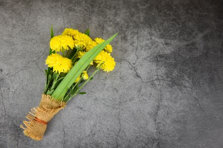 Bouquet yellow mum flowers spring and pandan wrapped in sack on dark plate background  Flowers respect