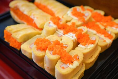 Sushi menu set Japanese cuisine fresh ingredients on tray  Japanese food sushi roll rice crab stick omelet with Tobiko egg is orange (flying fish roe) in the restaurant Imagens