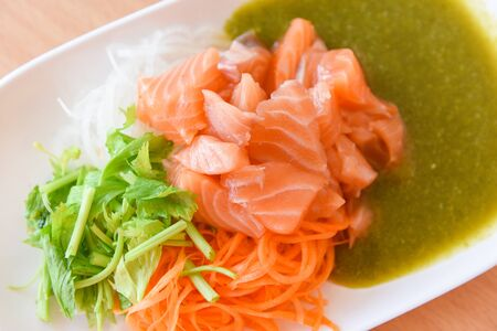 Salmon salad menu set Japanese cuisine fresh ingredients on plate  Japanese food raw sashimi salmon fillet with carrot celery seafood sauce in the restaurant