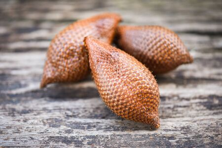 Salak on wooden background  Salak tropical fruit Salacca zalacca or Snake fruit palm