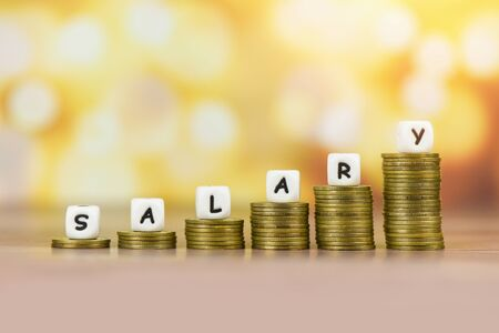 Payroll and salaries ladder increase growth money coins on table and success concept  salary text block with stacked coins on bokeh background