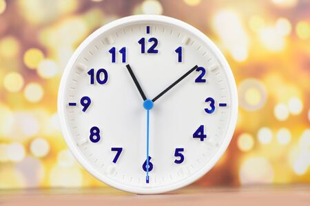 time concept  clock wall on wooden table and bokeh background , white round clock