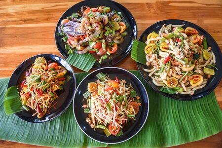 Papaya salad served on dining table  Green papaya salad spicy thai food on plate with fresh vegetables corn herbs and spices seafood shrimp crab noodles salted egg - Som tum Thai menu Asian food Imagens