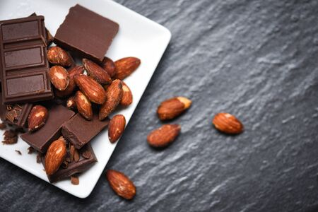 chocolate almonds nut on white plate on the dark background  chunks candy sweet dessert and snack