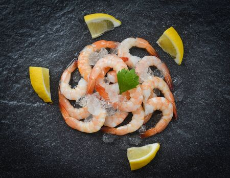 fresh shrimps served on ice in the dark plate  boiled peeled shrimp prawns cooked with lemon spices in the seafood restaurant
