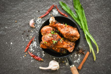 Grilled chicken legs barbecue with herbs and spices  Tasty roasted chicken legs on the pan with ingredients cooking food