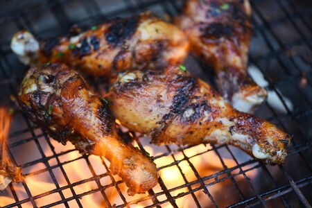 Grilled chicken legs barbecue with herbs and spices  Tasty chicken legs on the grill with fire flames marinated with ingredients cooking picnic outdoors Stok Fotoğraf
