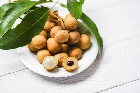 Longan fresh tropical fruit and green leaf in Thailand  Dimocarpus longan peel exotic fruits on white plate on wooden background Imagens