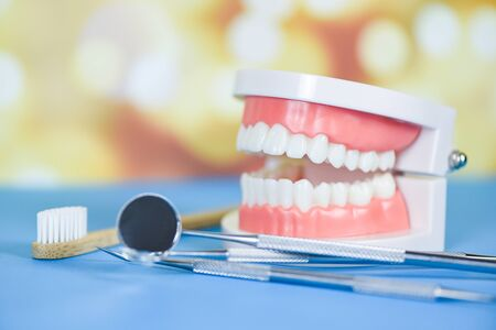 dentist tools with bamboo toothbrush dentures dentistry instruments and dental hygienist checkup concept with teeth model and mouth mirror oral health , selective focus