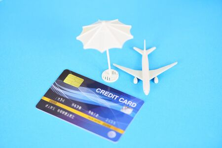 Insurance travel concept  Air travelling credit cards and umbrella on blue background