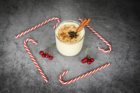 Eggnog delicious holiday drinks like themed parties with cinnamon and candy cane nutmeg for Traditional Christmas and winter holidays Homemade eggnog in glasses with red berries decorated table