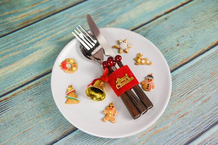 Christmas table place setting decoration with fork spoon and knife on white plate wooden dining table  Xmas New Year food lunch festive Christmas dinner holidays background themed party