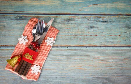Christmas table place setting decoration with fork spoon and knife on napkin on the wooden dining table Xmas New Year food lunch festive Christmas dinner holidays background themed party