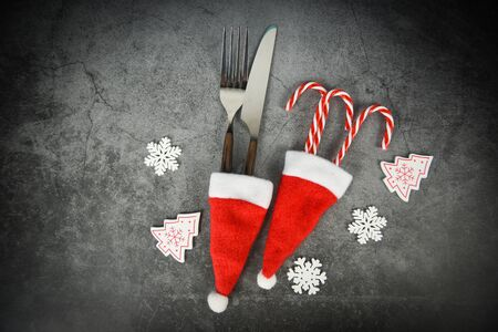 Christmas table place setting decoration with fork knife and candy cane in santa claus hat Xmas New Year food lunch festive Christmas dinner holidays background themed party