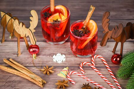 red mulled wine glasses reindeer decorated table  Christmas mulled wine delicious holiday like parties with orange cinnamon star anise spices for traditional christmas drinks winter holidays