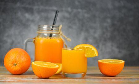 Orange juice in the glass jar and fresh orange fruit slice on wooden table  Still life glass juice on dark