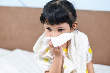 Asian little girl sick wrapped in handkerchief get cold and blow nose the flu season  child runny nose and sneezing blowing their nose and fevers at home