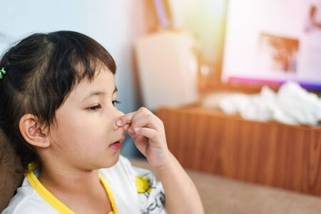 Asian little girl sick with hand holding the nose get cold and blow nose the flu season  child runny nose and sneezing blowing their nose and fevers at home Stock Photo