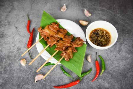 Grilled pork thai asian street food style  Slice pork skewer sticks grilled on banana leaf on white plate with sauce chilli garlic Stock Photo
