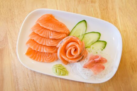 Japanese food raw sashimi salmon fillet with vegetable cucumber and wasabi in the restaurant  Salmon sashimi menu set Japanese cuisine fresh ingredients on plate , selective focus 写真素材