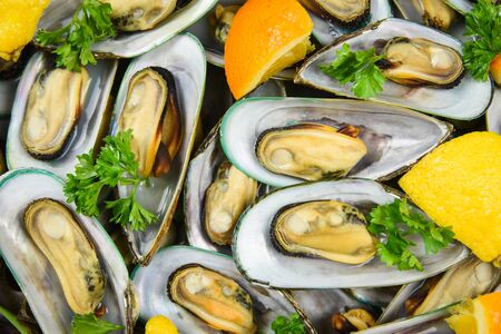 Mussels with herbs in pot with orange lemon parsley tomato in the table setting  Steamed mussels green shell served seafood delicious on dining table restaurant