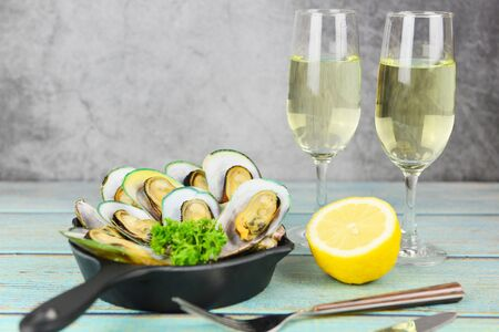 Mussels with herbs with lemon parsley in the table setting  Steamed mussels and wine glass served on white plate seafood sauce delicious on dining table restaurant 写真素材