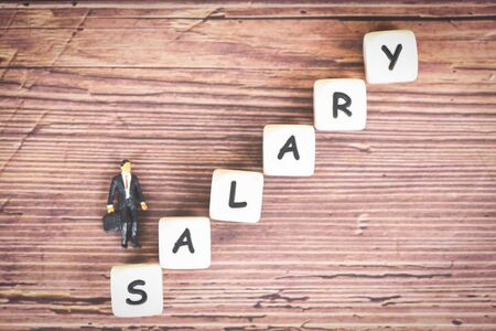 Payroll and salaries ladder increase growth money coins on table and success concept  salary text block with bussiness man raise the salary staircase Banco de Imagens