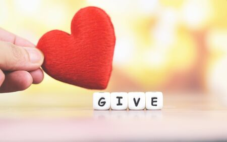 Give love with red heart in hand for donate and philanthropy health care love organ donation family insurance world heart day world health day  Concepts of sharing giving or valentines day