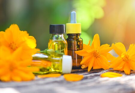 Aromatherapy herbal oil bottles aroma with flower yellow on nature green background  Essential oils natural for face and body beauty remedies on wooden table and organic minimalist lifestyle Zdjęcie Seryjne
