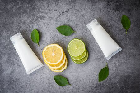 Lotion bottle natural for face and body beauty remedies and organic minimalist lifestyle with lemon lime slice and green leaves herbal formulations , top view
