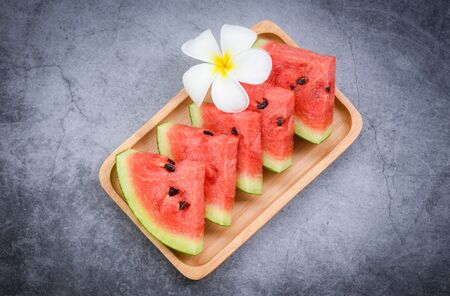 Fresh watermelon slice and white flower on black background  watermelon tropical fruit on wood tray , selective focus
