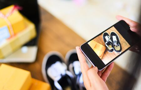 young woman taking photo sneakers with camera smartphone for post to sell online on the internet market website  selling online ecommerce shipping online shopping delivery and order concept Banco de Imagens