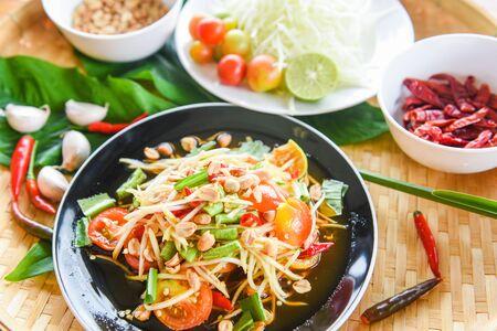 Papaya salad on black plate  Close up of green papaya salad spicy thai food and ingredients on the table  - Som tum Thai
