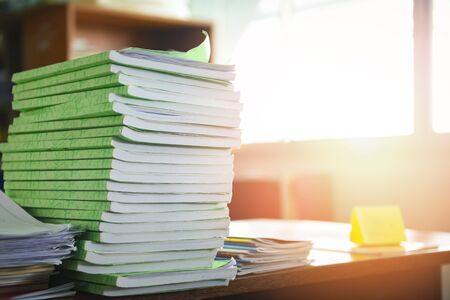 Lot of work document file working and book stacks of paper files searching information on work desk office  business report papers piles unfinished on the table