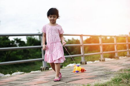 Child having fun playing outside Asian kid girl happy with toys in the park playground  International Childrens Day  Banco de Imagens