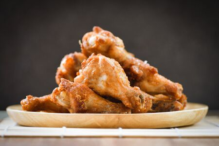Fried chicken wings on wooden plate  Baked chicken wings BBQ on black background
